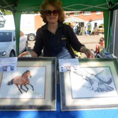 Gerri sowing the Henry Fraser SCI Mouth Artist kindly donated auction items: WILD HORSE & HAWKEYE